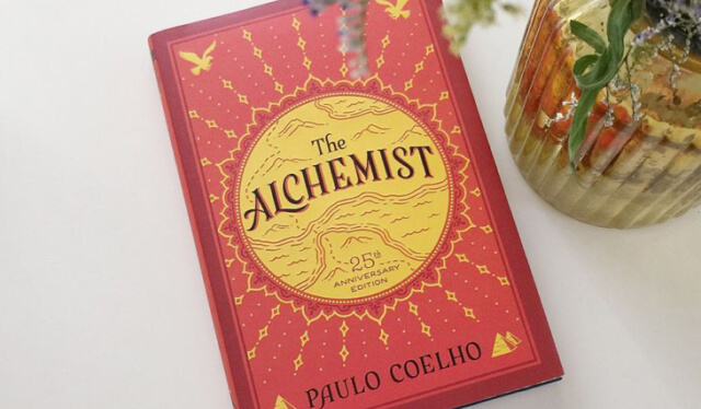 Cover of a red and yellow book - The Alchemist by Paulo Coelho - on a white table
