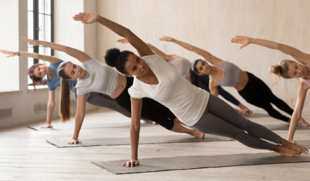 Group of six women practice side plank in a yoga class