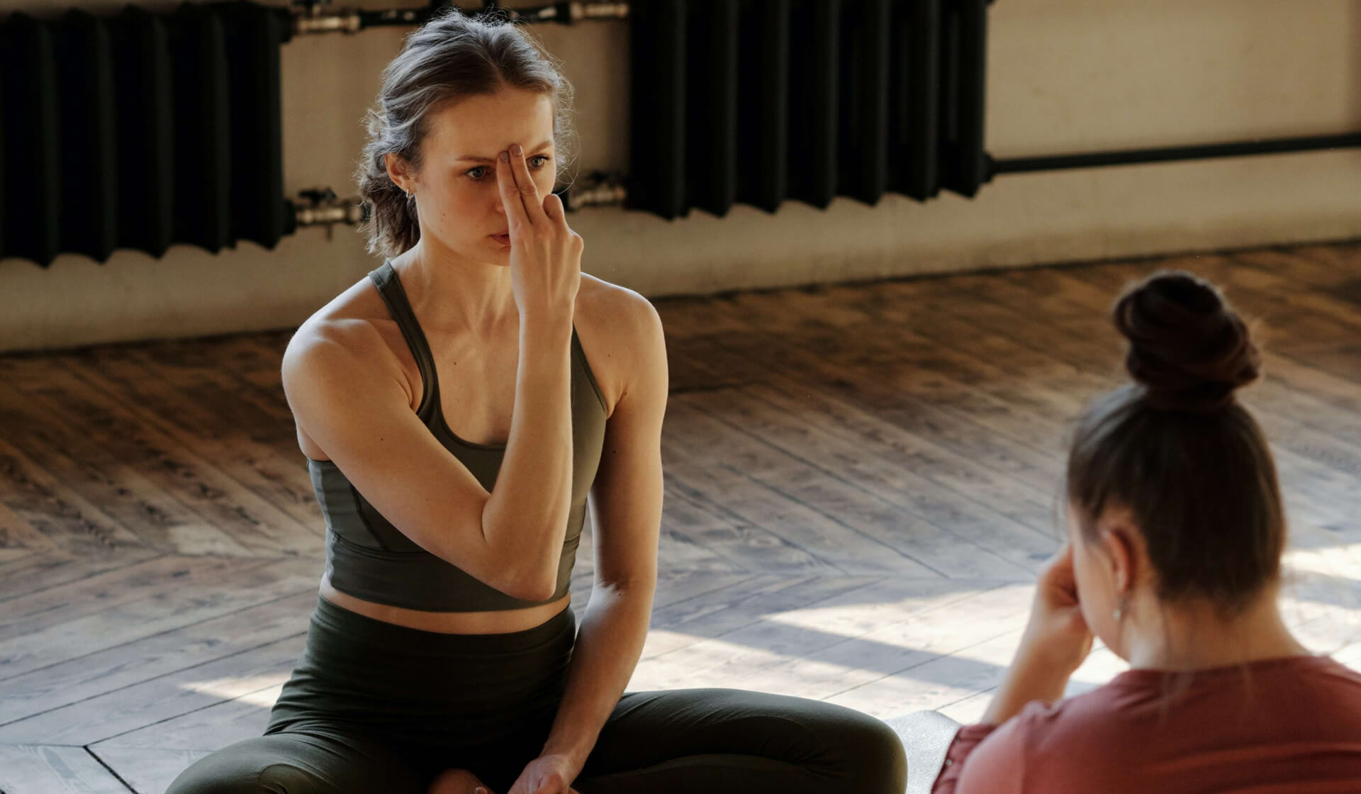 Woman yoga teacher sitting cross-legged teaching nadi shodhana (alternate nostril breath) to another woman