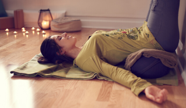 Woman lying on a blanket on the floor with her legs up the wall and a yoga bolster under her pelvis
