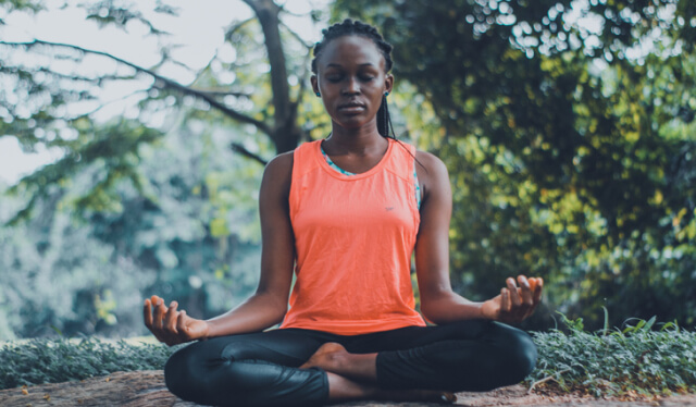 Woman in black leggings and an orange tank sitting on the ground in meditation with her eyes closed