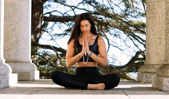 Woman in black leggings and a blank tank sitting on the ground in meditation with her eyes closed and her hands at her heart