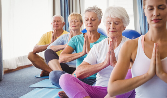 Group of elderly yogis sitting cross legged on the floor with their hands at their hearts