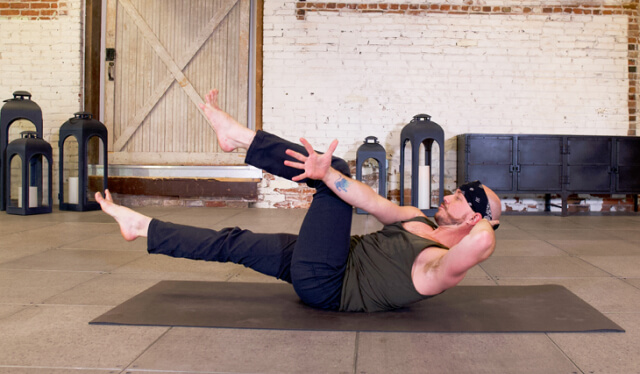 Male yoga teacher practicing an oblique twist while lying on his back on a black yoga mat