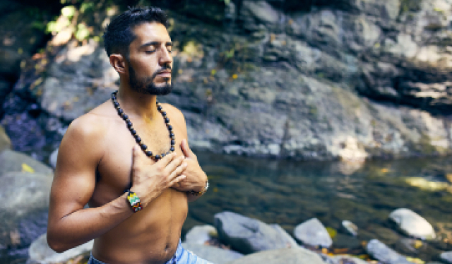 Man sitting on a rock beside a stream with his eyes closed and both hands resting over his shirtless chest