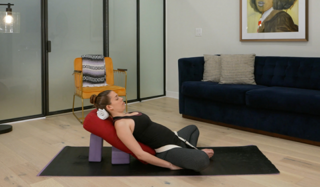 Woman yoga teacher reclined over a bolster in reclining bound angle pose in a living room in front of a blue couch