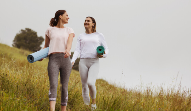 Two women wearing yoga clothes and carrying yoga mats walking in a field