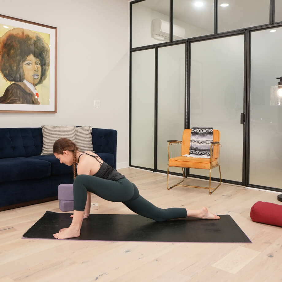 Yoga teacher practicing a lunge pose on a black yoga mat in a living room