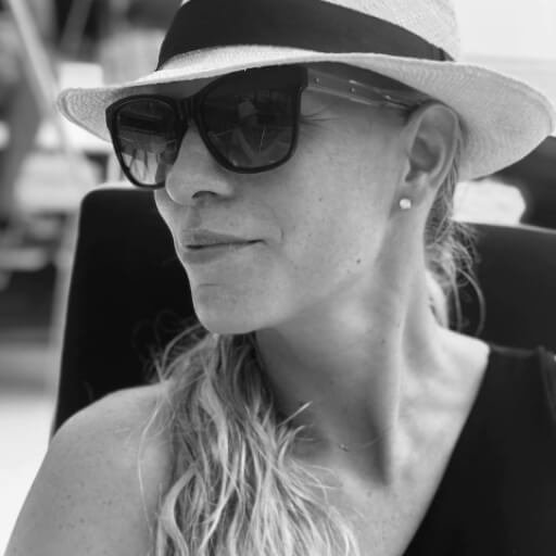 Young woman in sunglasses and a fedora smiling