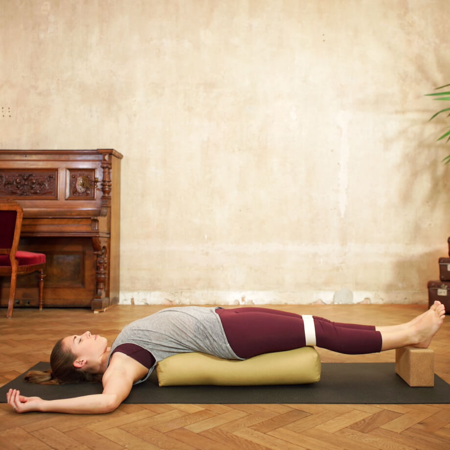 Yoga teacher resting over a bolster and a yoga block in a restorative yoga pose