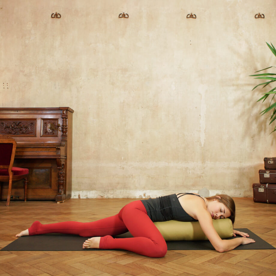 Yoga teacher laying over a yoga bolster with her knee bent in half frog pose in red yoga pants and a black tank
