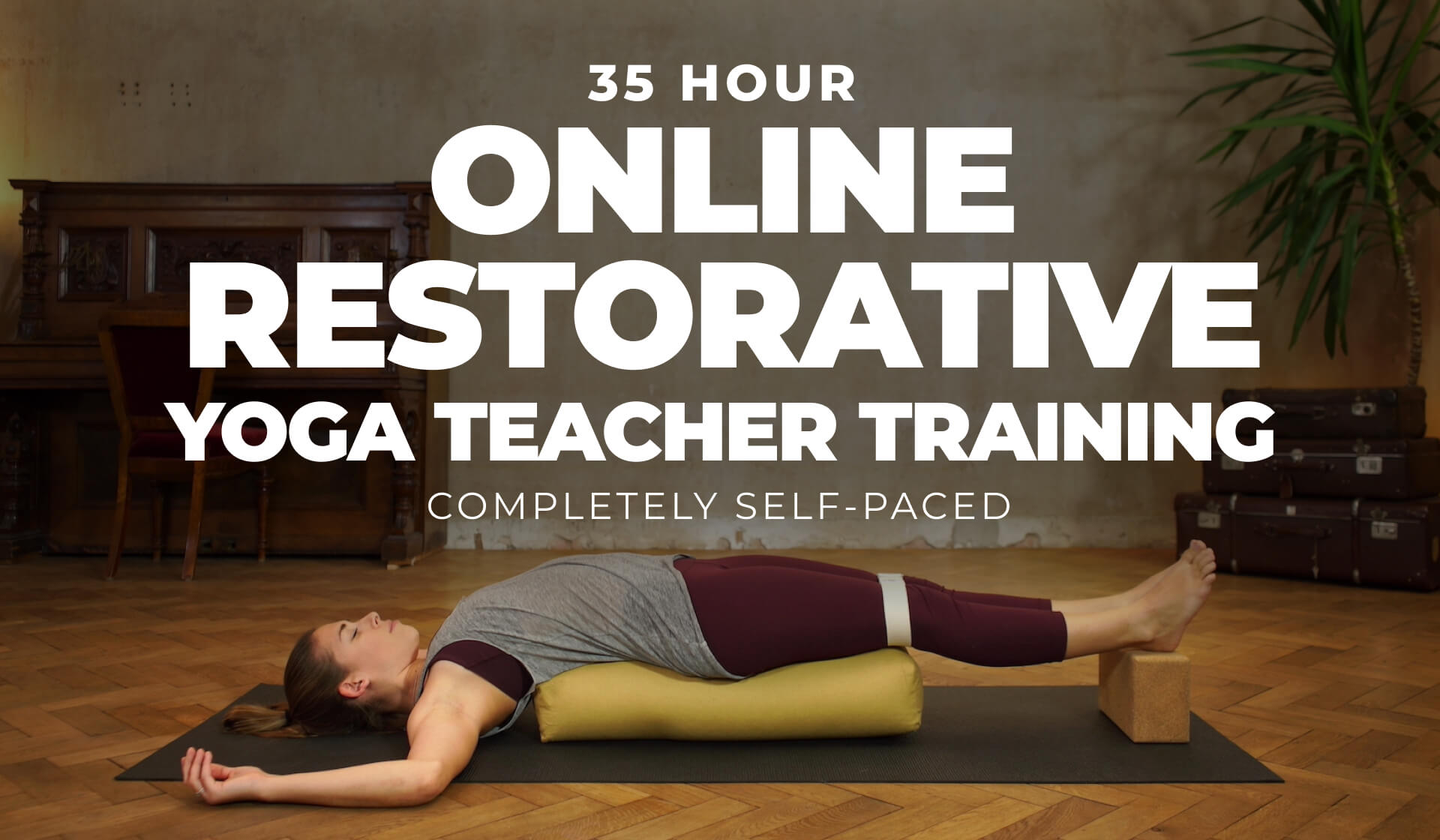 """Yoga teacher dressed in all maroon pants and a gray tank relaxing over a yoga bolster in a restorative yoga pose with the text """"35 Hour Online Restorative Yoga Teacher Training completely self-paced"""" written on the image"""