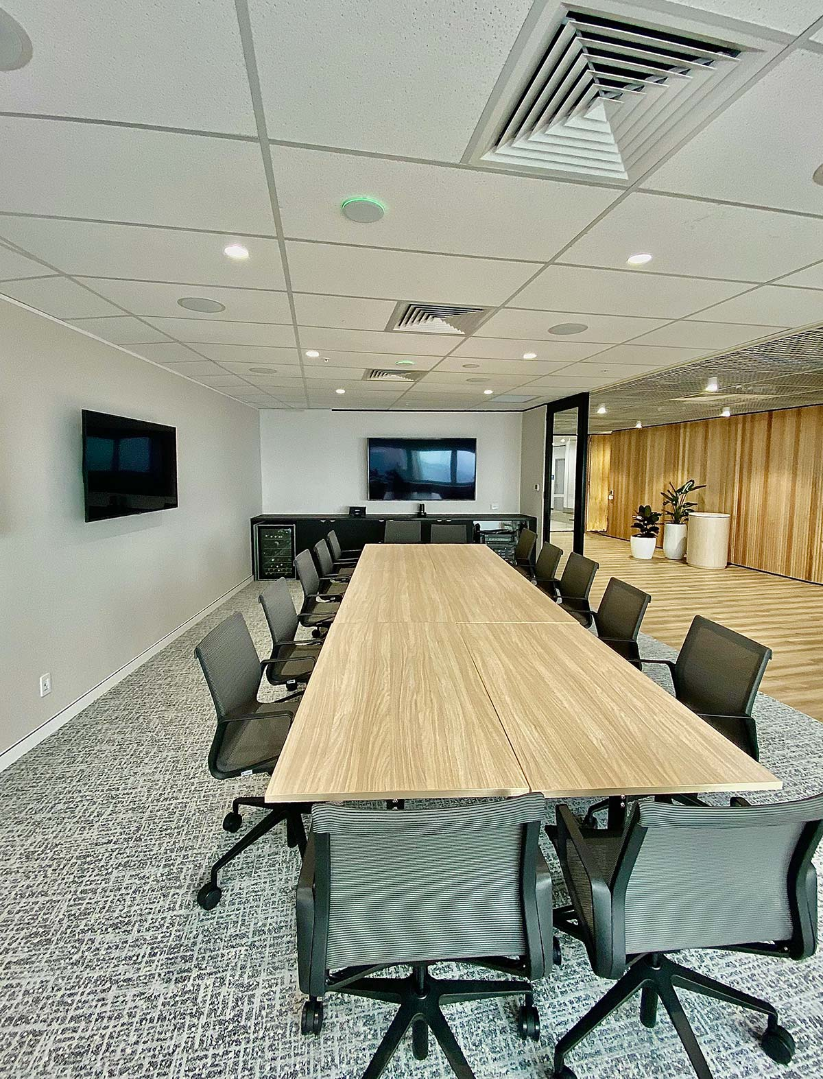 video conference boardroom with TV screens on wall
