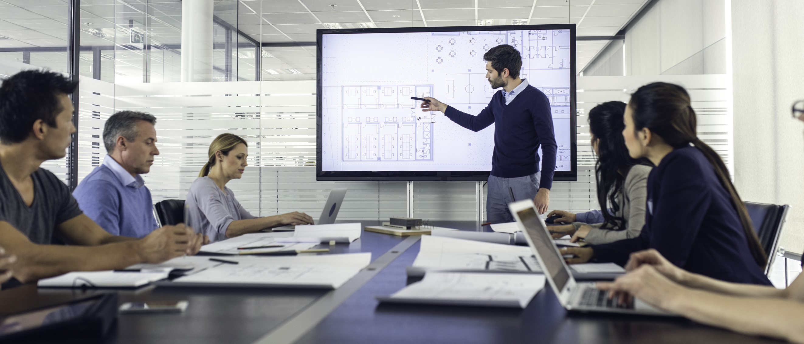 man pointing to floorplans on interactive touchscreen