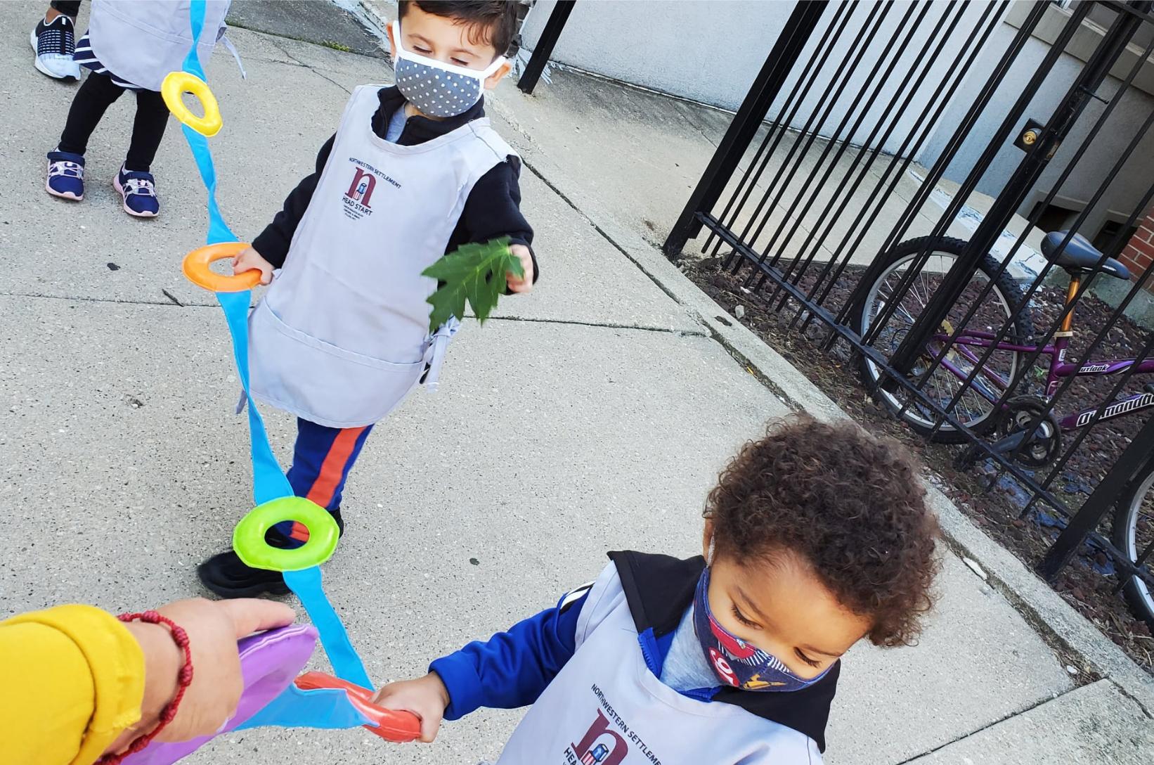 Young children wearing masks walk down the sidewalk