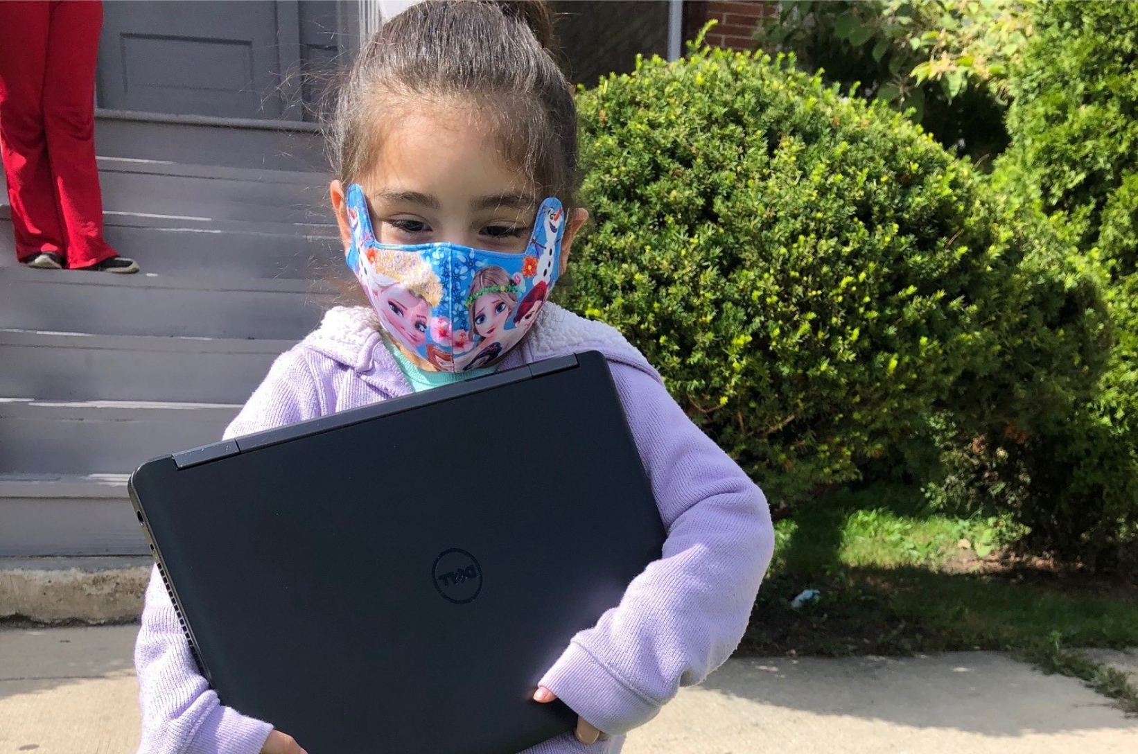 A young girl in a mask holds a donated laptop