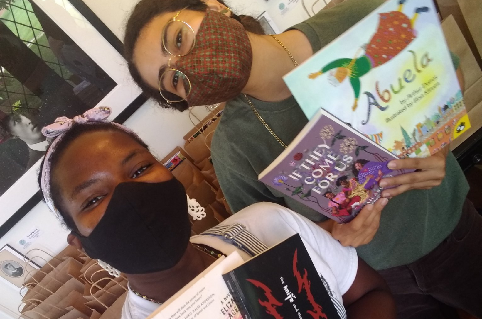 Two women in masks holding up children's books