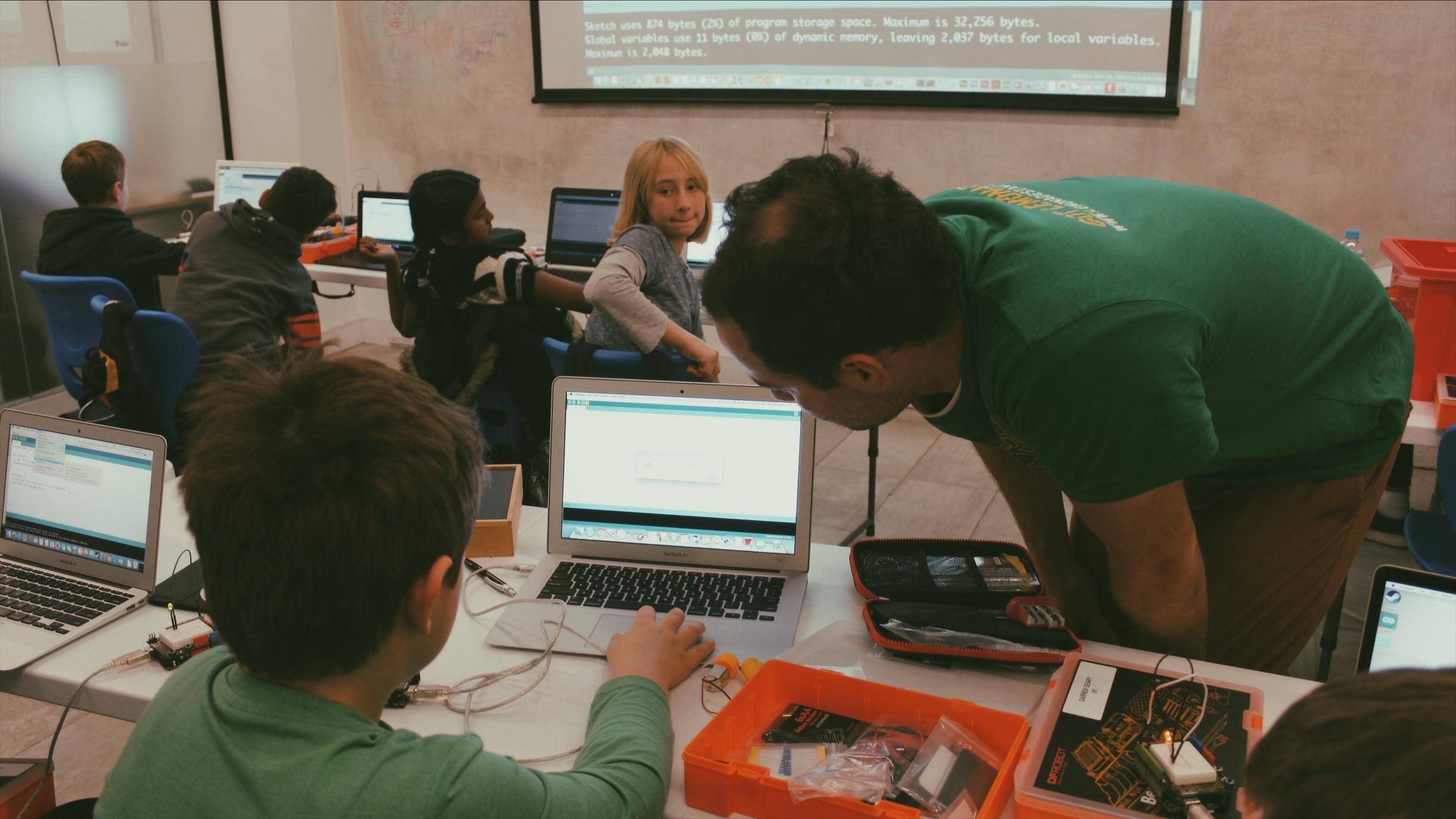 Lemonade Stand Kids Coding: a facilitator teaches a boy how to code