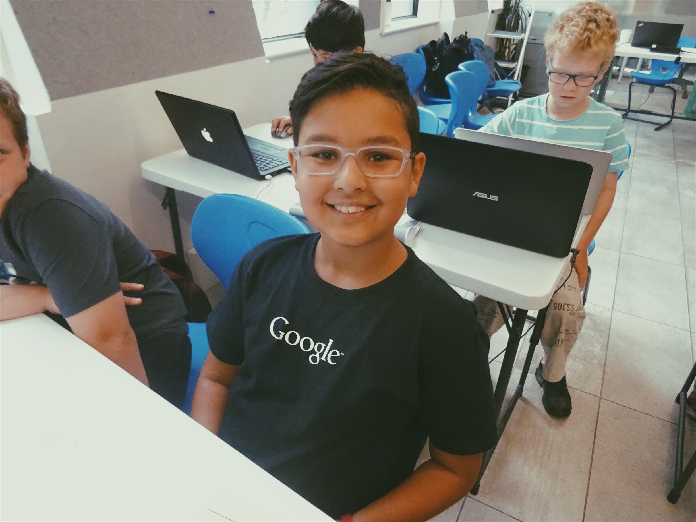 Lemonade Stand Kids Coding: a boy wearing a Google shirt smiling