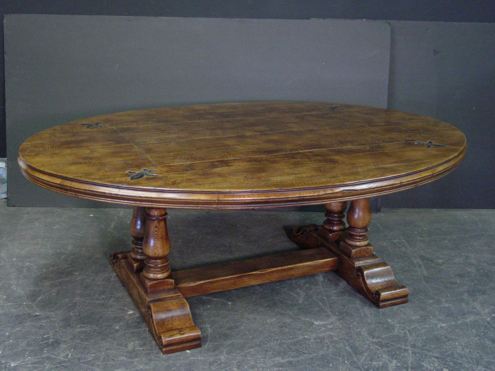 Antique finish oval dining table with fleur de lis details