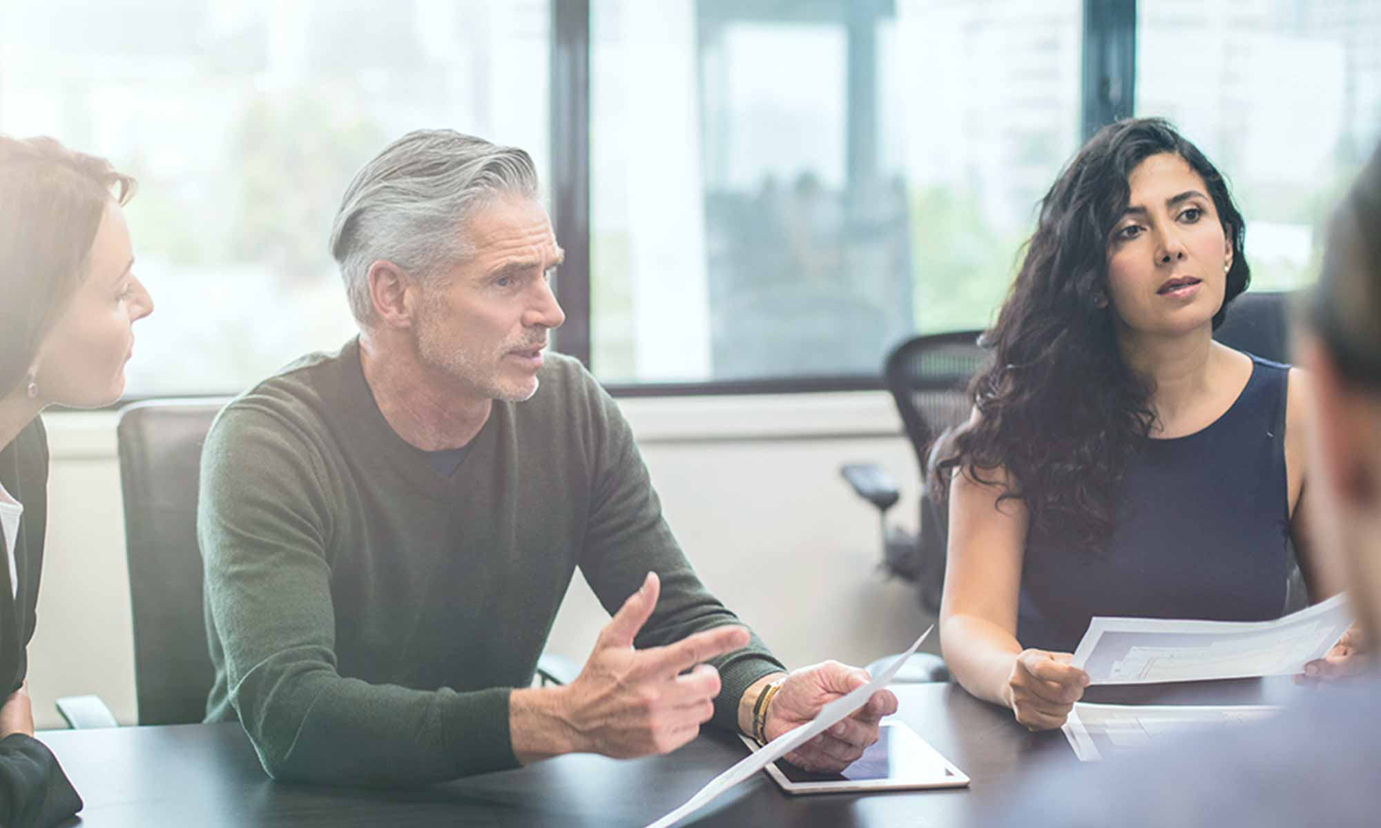 man and woman having serious discussion with colleagues