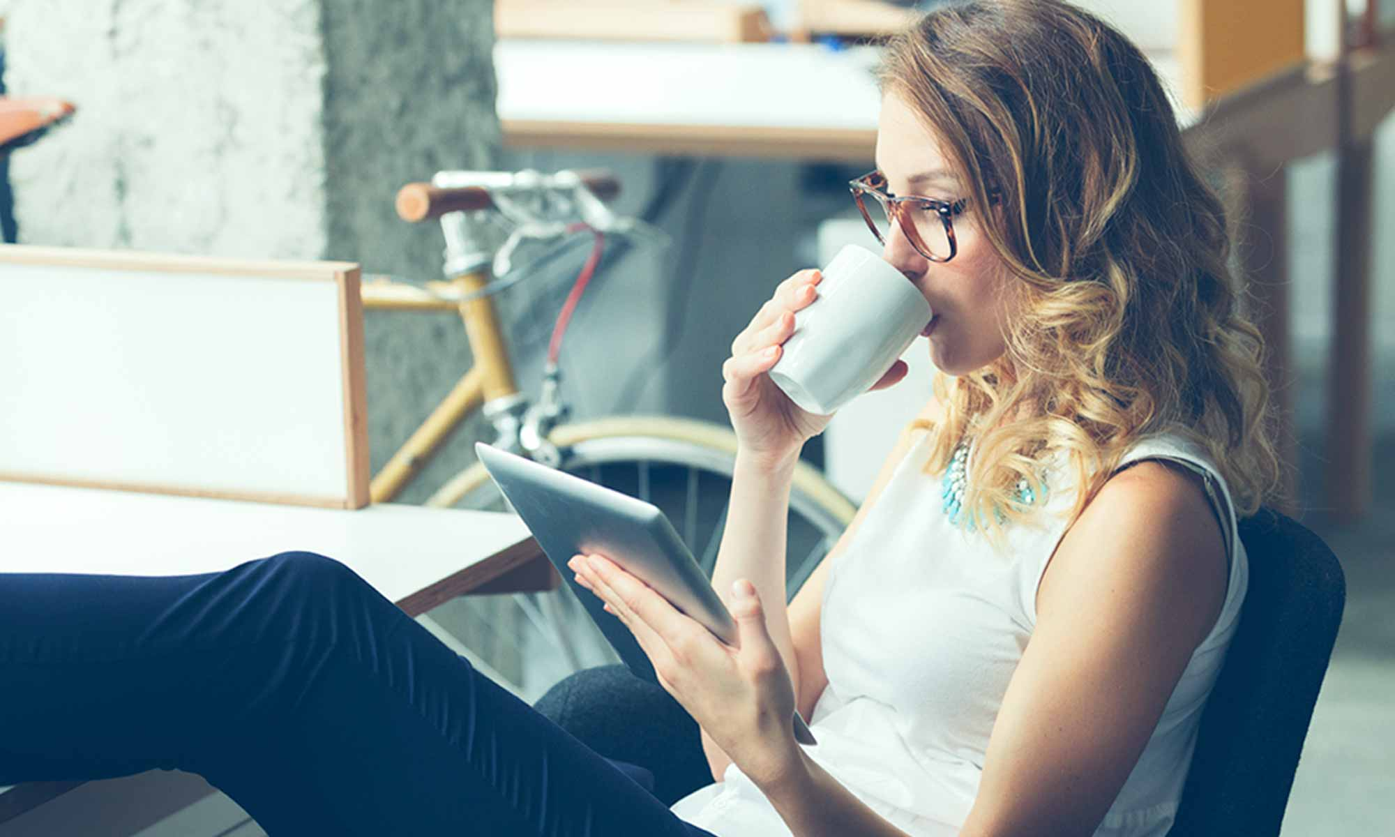 woman reading on tablet device sipping from mug