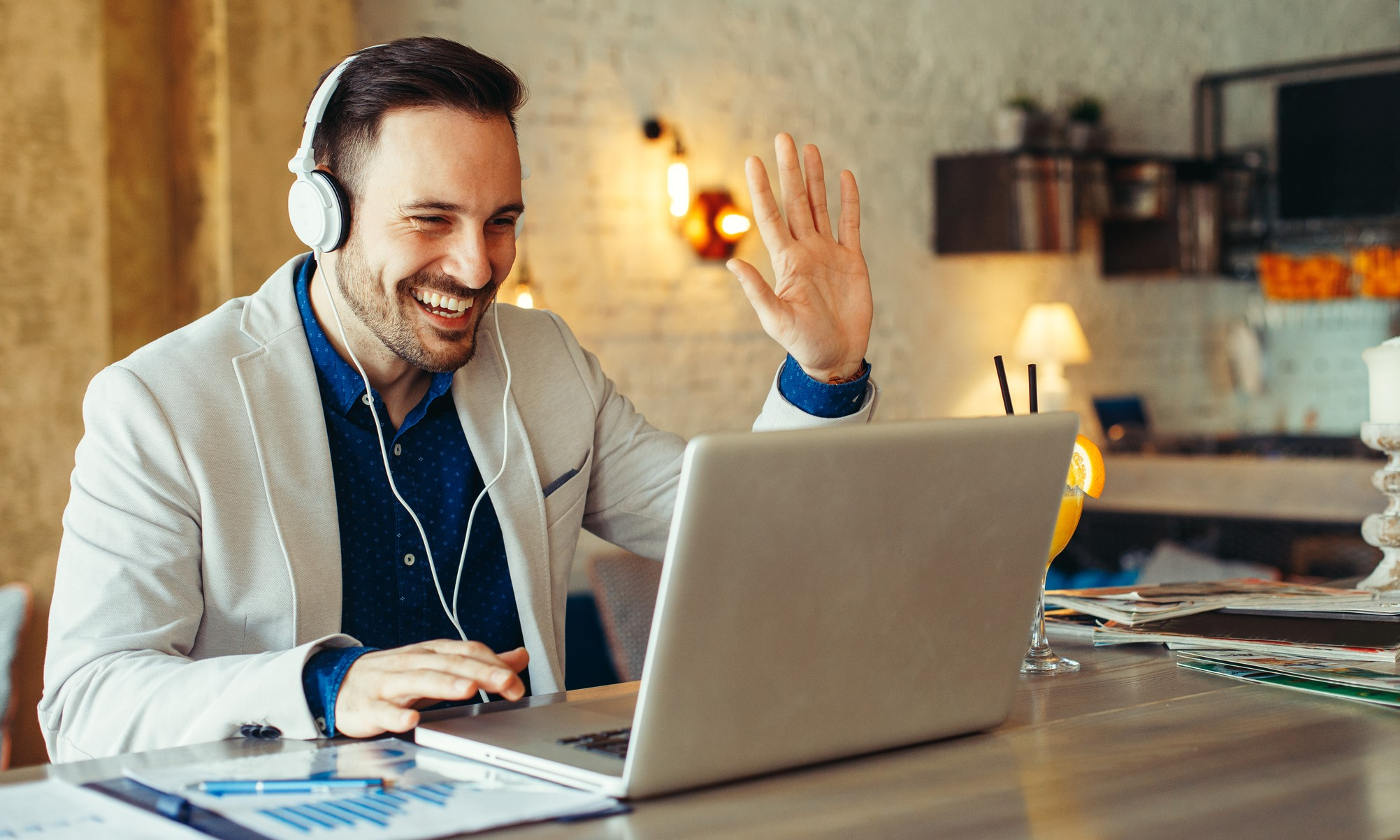 man wearing headphones waving to participant on desktop video conference