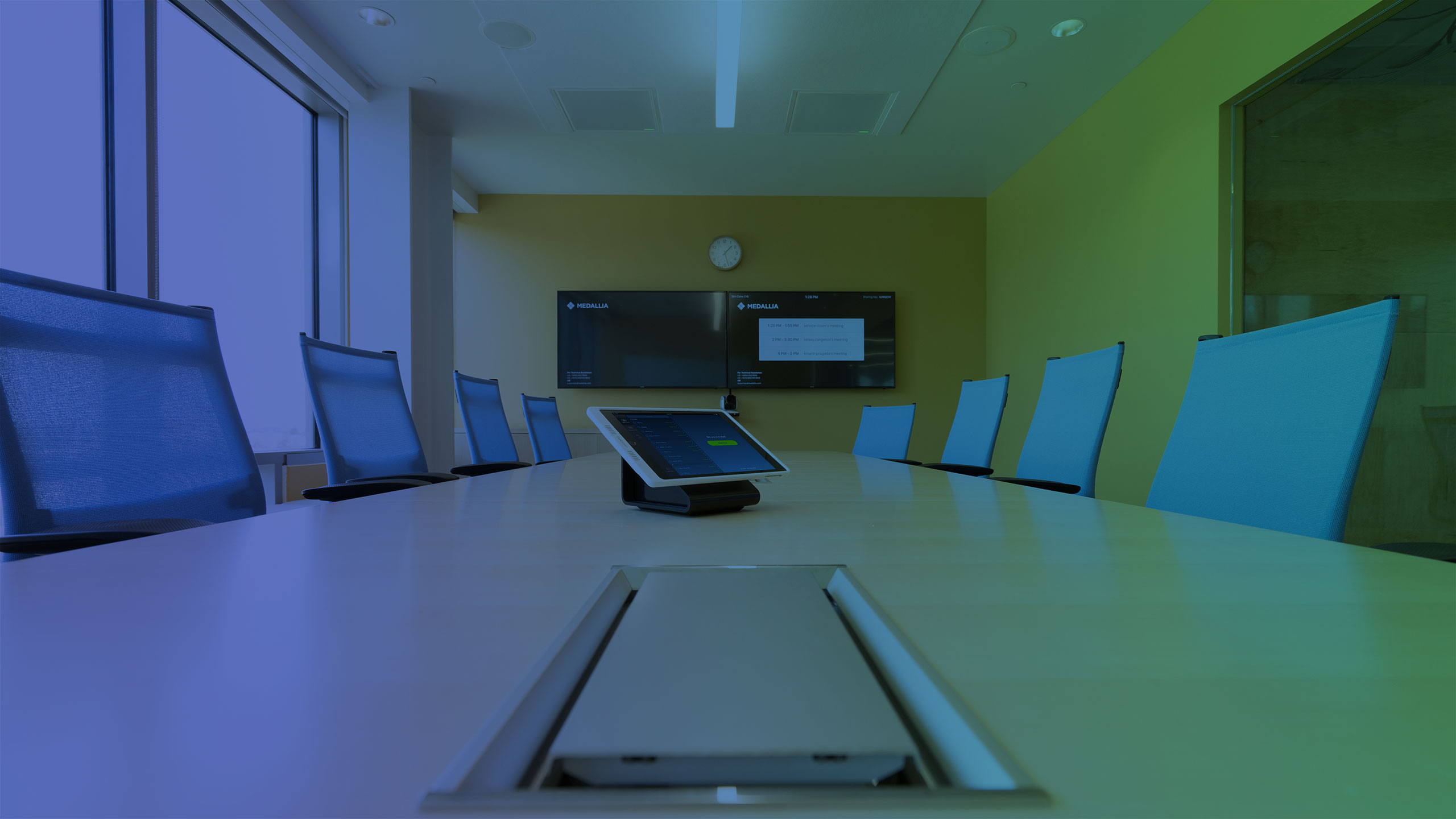 boardroom meeting table and video conferencing TVs mounted on wall
