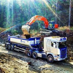Lasting av grå lastebil av graver