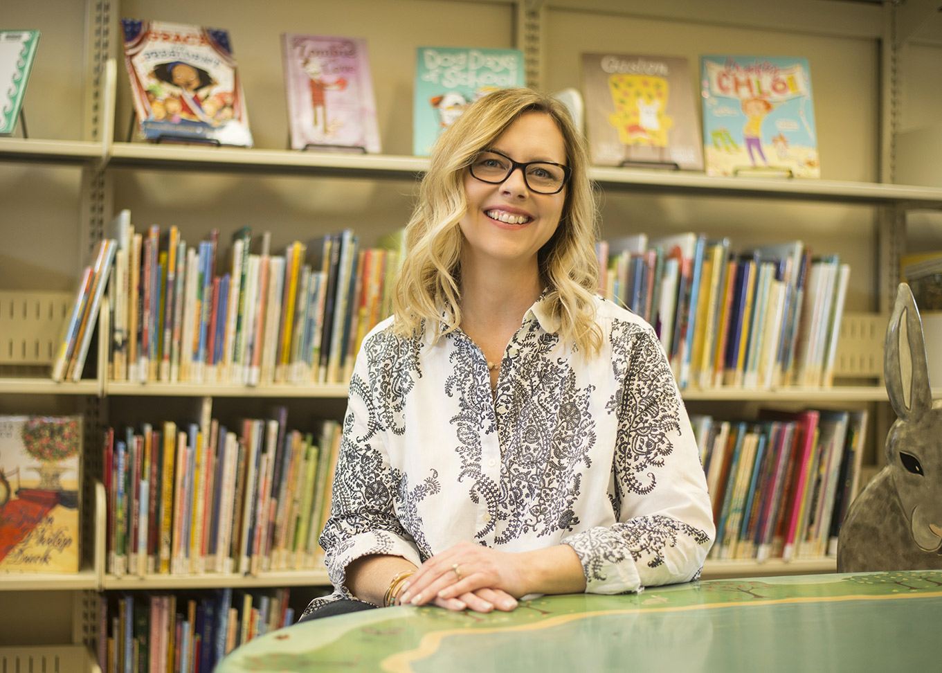 Photograph of NY Times bestselling children's author Kelly DiPucchio, who is seated at a table with four shelves of books in the background.  The top bookshelf showcases 5 books she has written herself