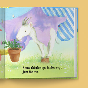 White goat near a clothesline of hanging blankets, eating thistle tops out of a flower top. Rhyming text above.