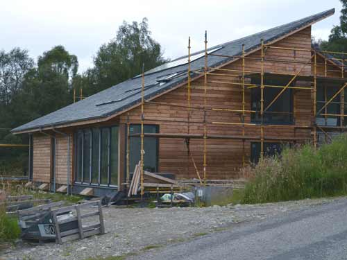 Clad in locally sourced larch, the unique design features a large, monopitch slate roof