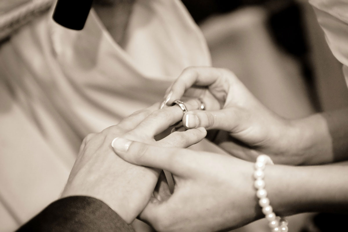 bride placing ring on grooms hand