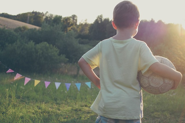 kid with soccer ball at sunset
