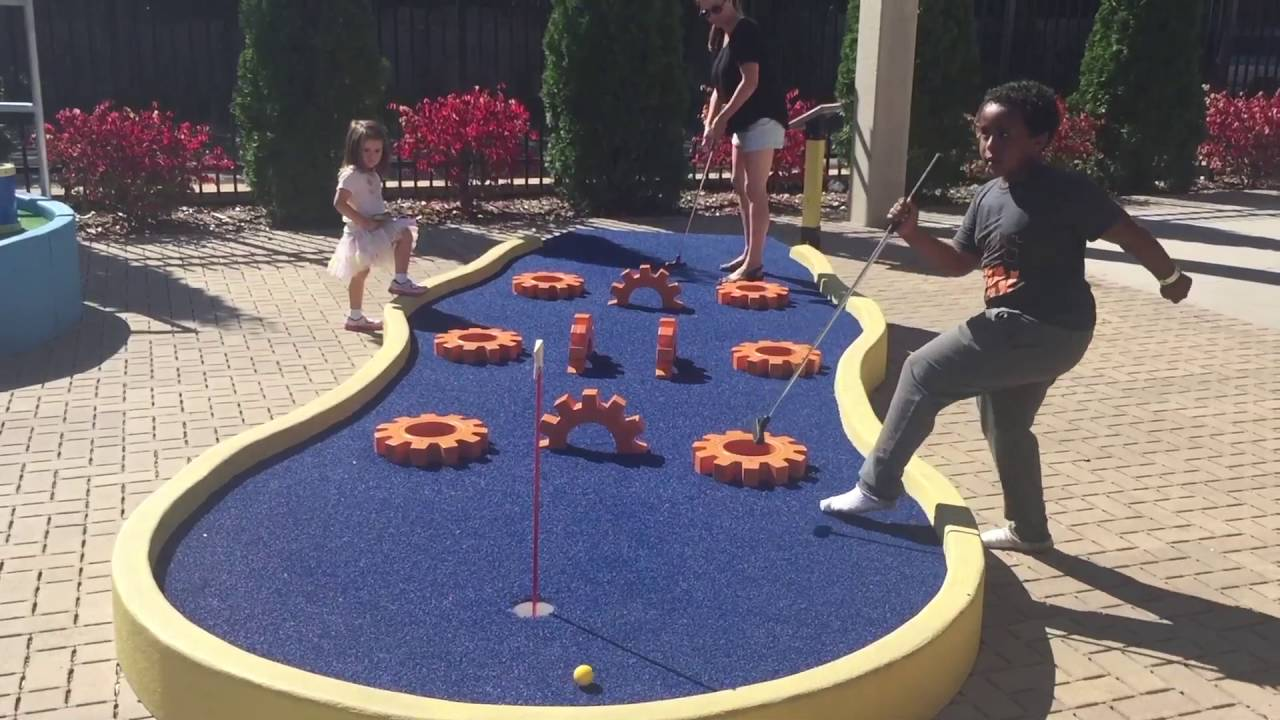 parent with two kids playing minigolf