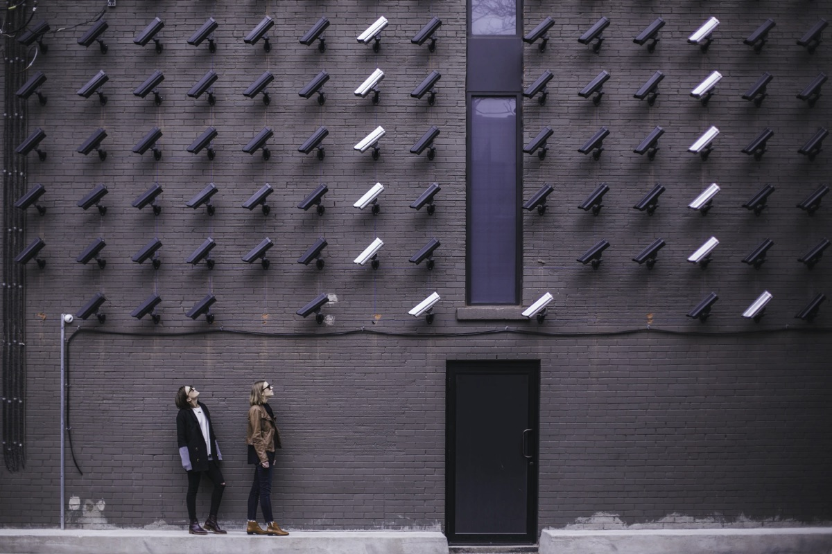 Two individuals looking at a huge wall filled with security cameras