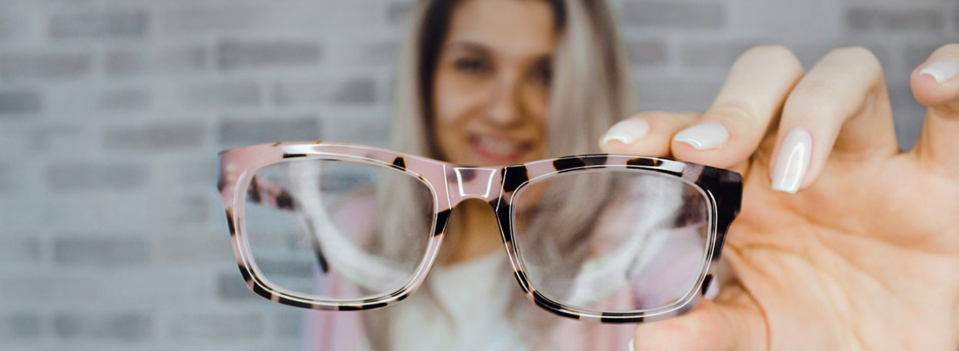 woman holding pair of glasses