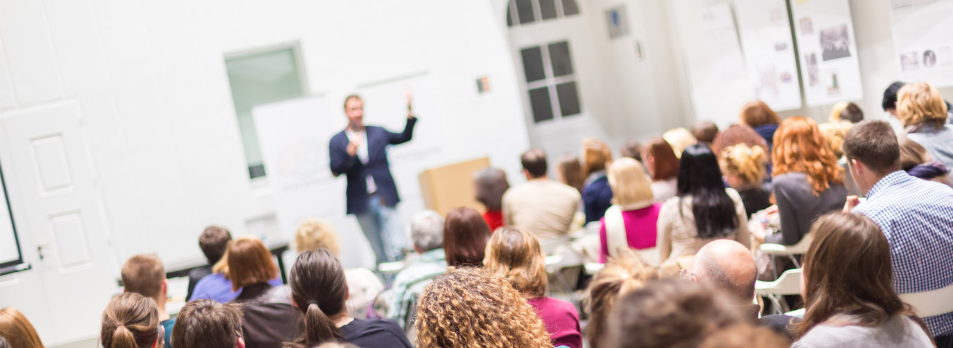 Man giving presentation in front of medium sized crowd indoors.