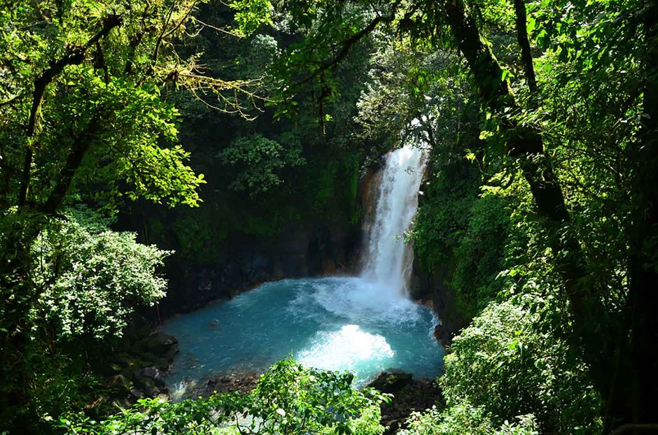 a picture of Casta Rica rio celeste waterfall with forest around it
