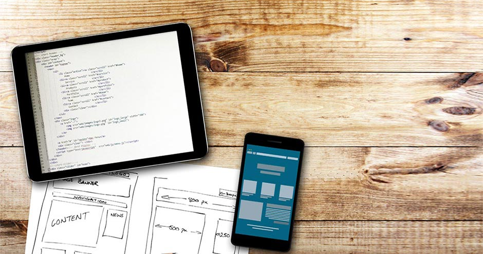 Imagem de um tablet e um smartphone em cima de uma mesa com estrutura html de um site.