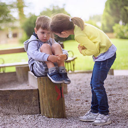 child comforting smaller child on playground
