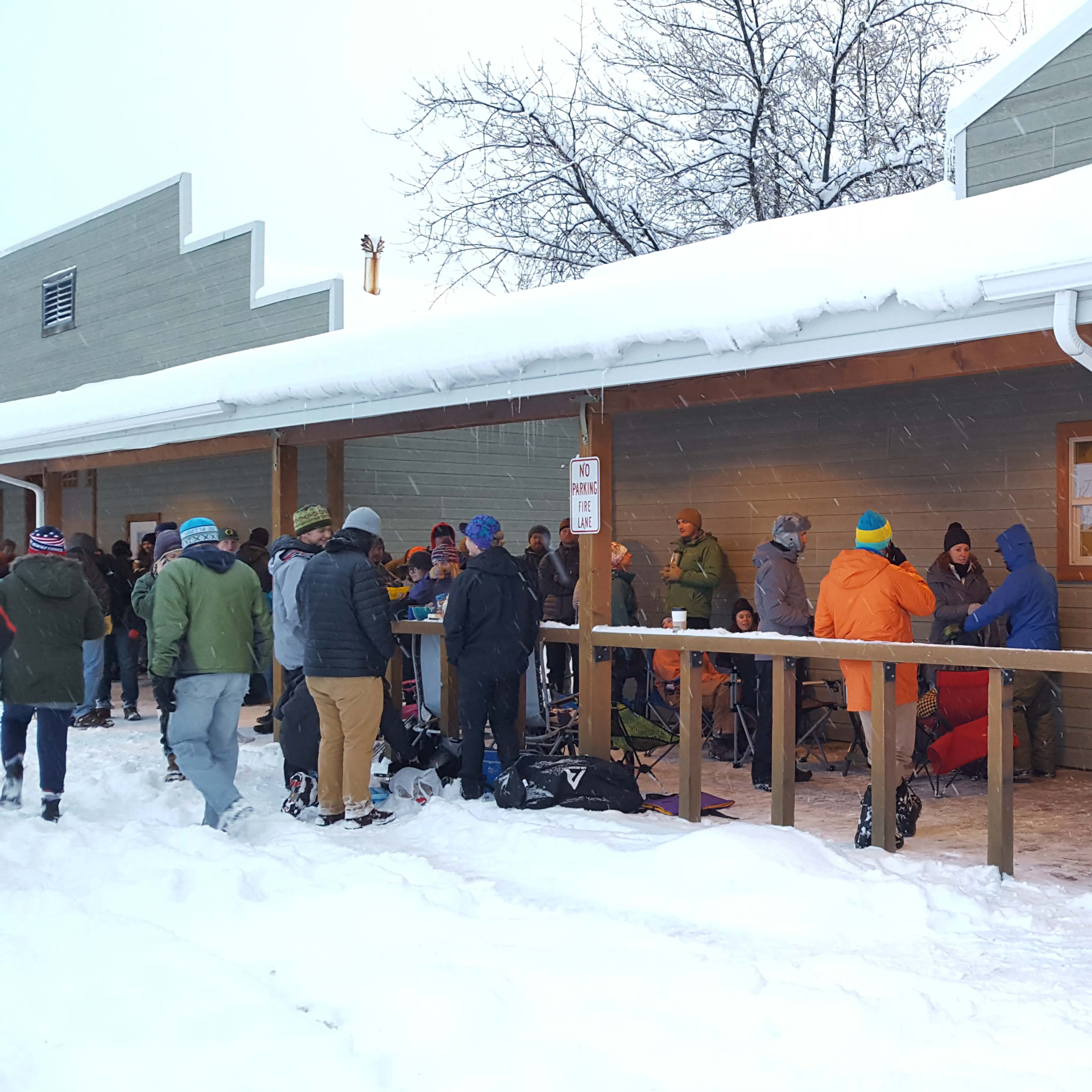 A line of people waiting outside of a building for ski swap.