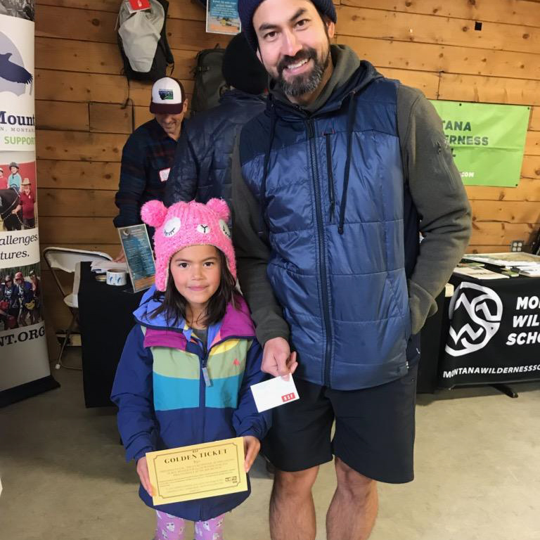 A little girl with her dad picking up her golden ticket prize.