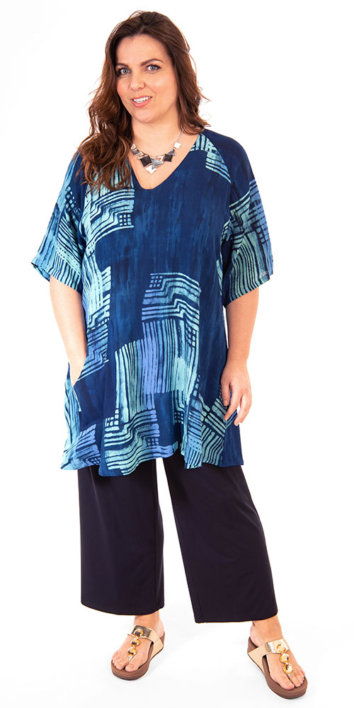 This image shows a model wearing a v neck long patterned viscose tunic with pocket from Angel Circle paired with jersey crop trousers from Q'neel in navy.