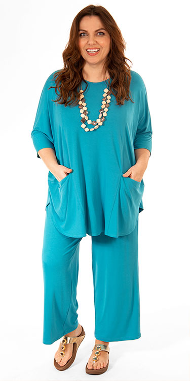 This model is wearing a fabulous batwing top teamed with matching crop jersey trousers by Q'neel. Plus sizes from Bakou.