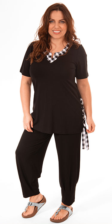 This model is wearing a See You t-shirt with check detail on the neck and check ribbon detail on the side paired with Q'neel harem trousers in black.