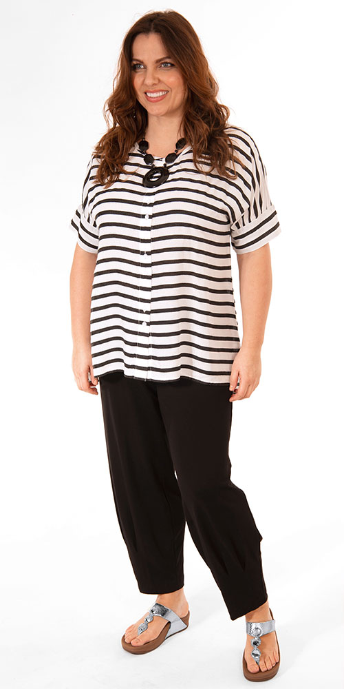 This image shows a model wearing a Masai Lesha striped short sleeved shirt available up to size 22 paired with Q'neel jersey harem trousers in black.
