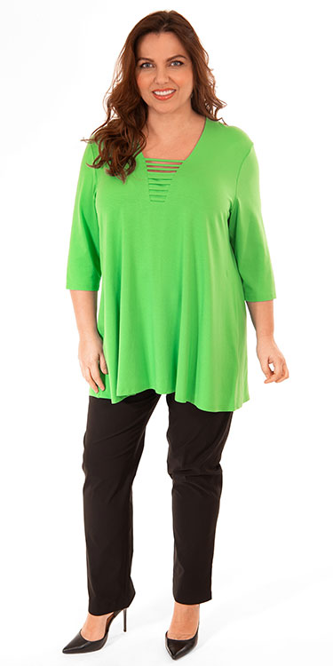 This model is wearing a bright green t-shirt by Doris Streich. It is A-line and has a criss cross neck feature. It has been paired with Mona Lisa lightweight narrow trousrs in black.