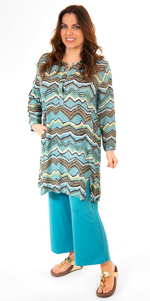 This image shows a model wearing a stylish zig zag Gyvi tunic from Masai paired with Q'neel jersey crop trousers in teal