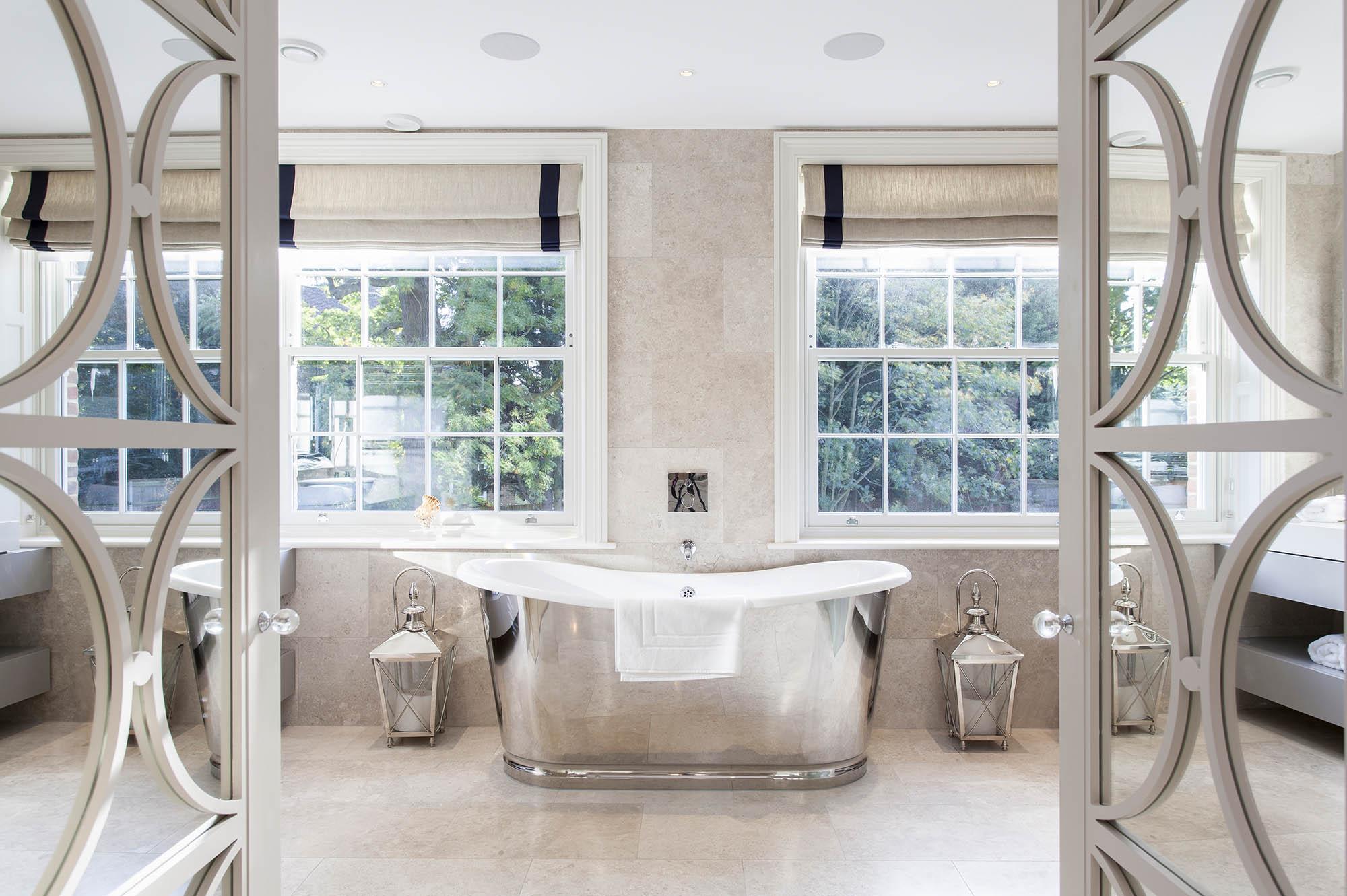 Modern luxury bathroom with silver freestanding bath, sash windows and internal french doors